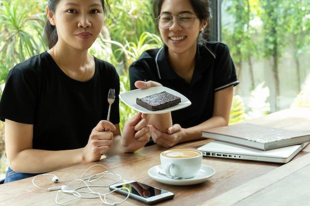 Female friends having coffee break with brownie cake in coffee shop.