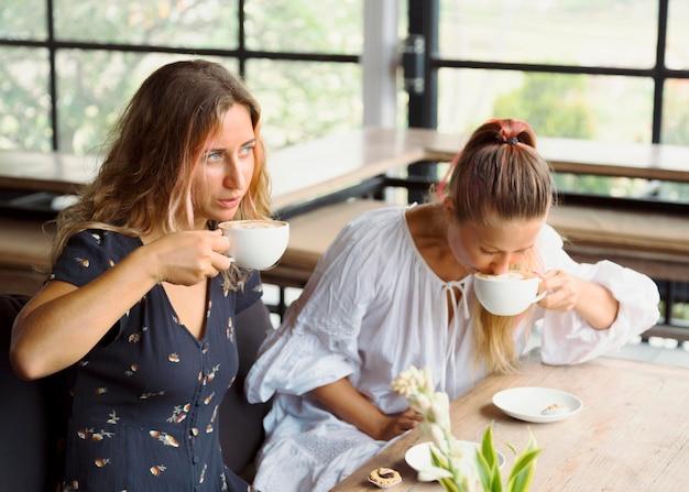 Подруги вместе пьют кофе