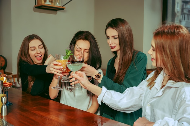 Amici femminili che hanno un drink al bar. sono seduti a un tavolo di legno con cocktail. sono bicchieri tintinnanti