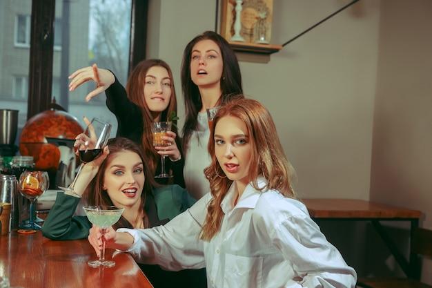 Amici femminili che hanno un drink al bar. sono seduti a un tavolo di legno con cocktail. indossano abiti casual.