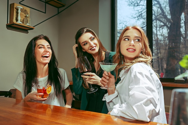 Female friends having a drinks at bar. they are sitting at a wooden table with cocktails. they are wearing casual clothes.
