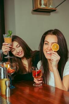 Amici femminili che hanno un drink al bar. sono seduti a un tavolo di legno con cocktail.