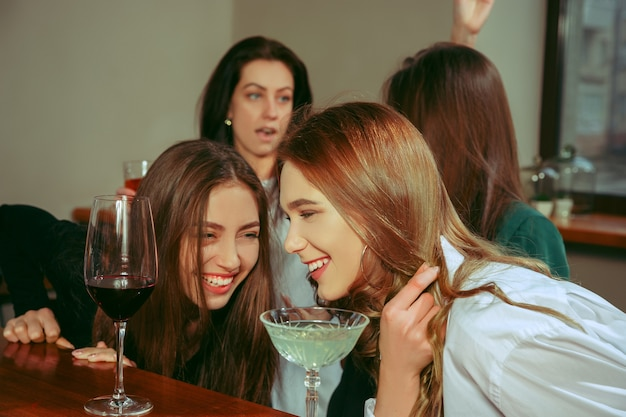 Female friends having a drinks at bar. they are sitting at a wooden table with cocktails.