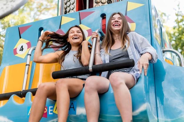 Amici femminili che hanno divertimento nel parco di divertimenti