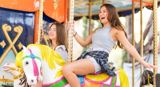 Female friends having fun on the carousel