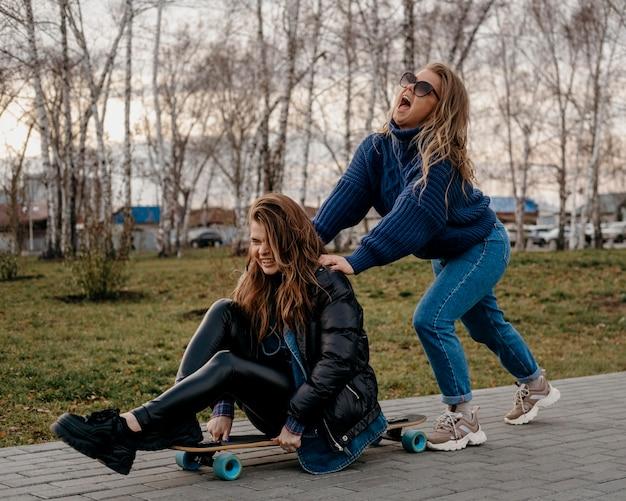 Amici femminili che hanno divertimento all'aperto con gli skateboard