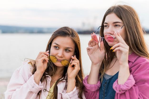 Amici femminili che hanno divertimento insieme in riva al lago