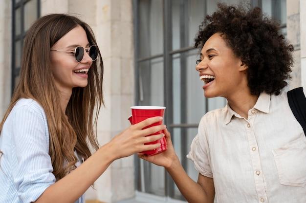 プラスチック製のコップと屋外で一緒に楽しんでいる女性の友人