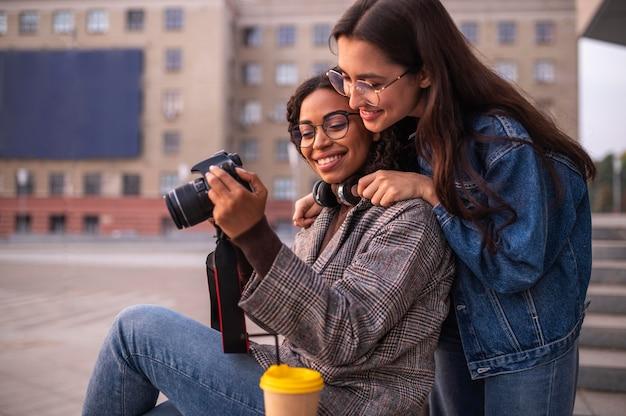 Amici femminili che hanno divertimento insieme alla macchina fotografica