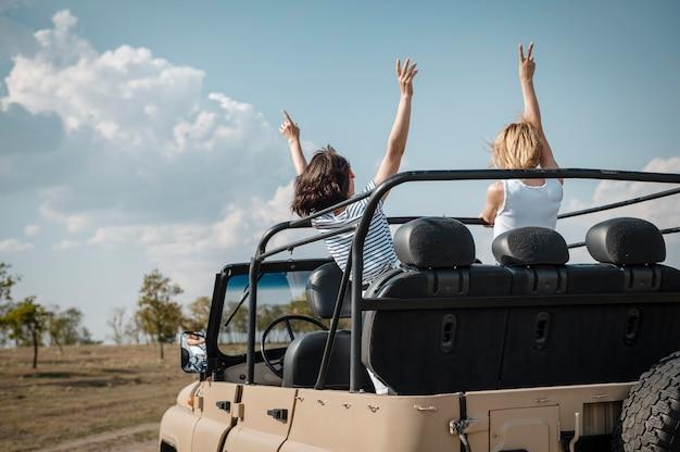 Amici femminili che hanno divertimento viaggiando in auto