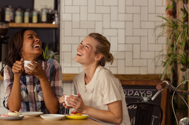 Female friends having fun while having coffee