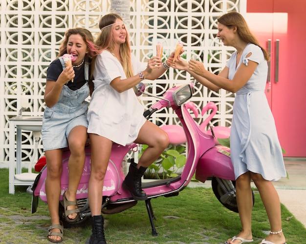 Amici femminili che mangiano gelato sul motorino