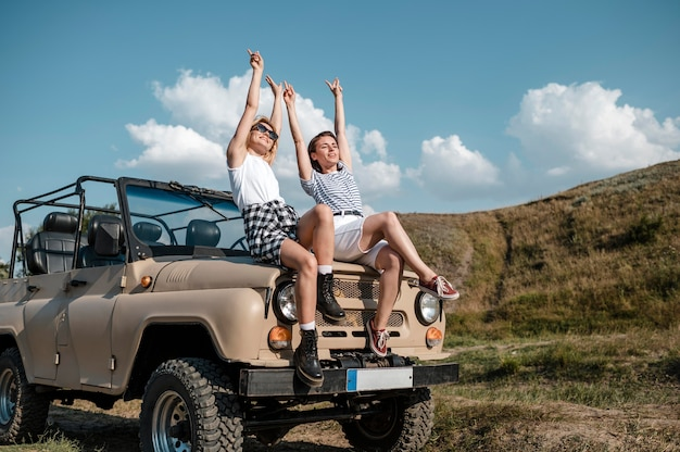 Female friends having a nice time while traveling by car