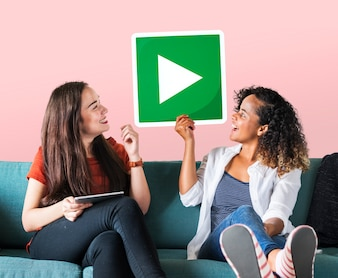 Female friends holding a play button