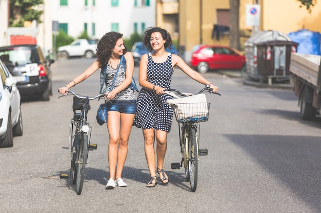 Female friends holding bikes and walking in the city
