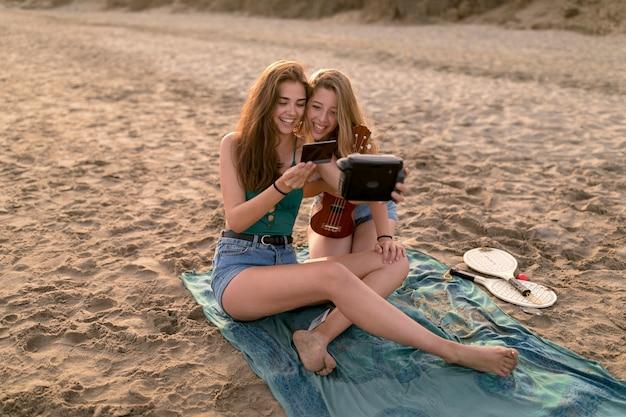 Female friends holding photo taking self portrait at beach
