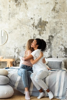 Female friends hugging each other with copy space