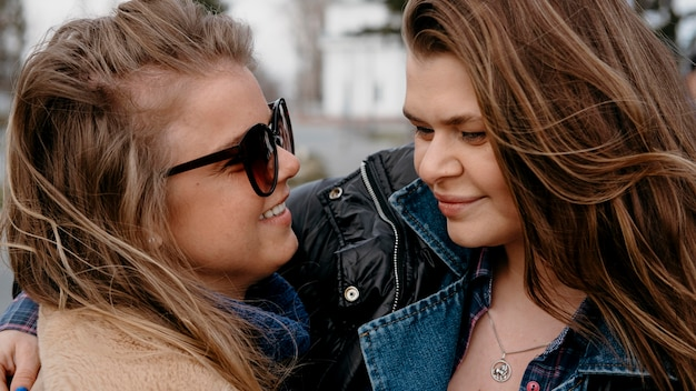 Female friends hugging together outdoors