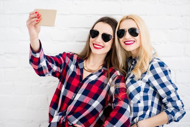 체크 무늬 셔츠를 입은 여자 친구가 흰 벽 배경에 전화기를 들고 셀카 초상화를 만들고 있다