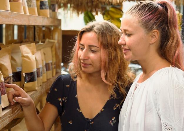 Подруги в магазине ищут продукты на полке