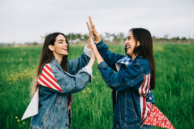 Female friends laughing on grass with american attributes