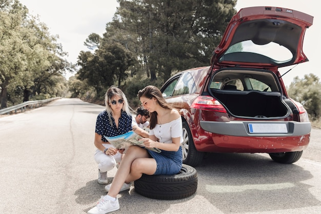 Female friends looking at map sitting near the broken down car on road