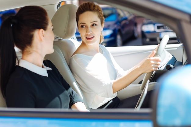 Подружки. милая приятная привлекательная бизнесвумен сидит за рулем и смотрит на коллегу, находясь с ней в машине