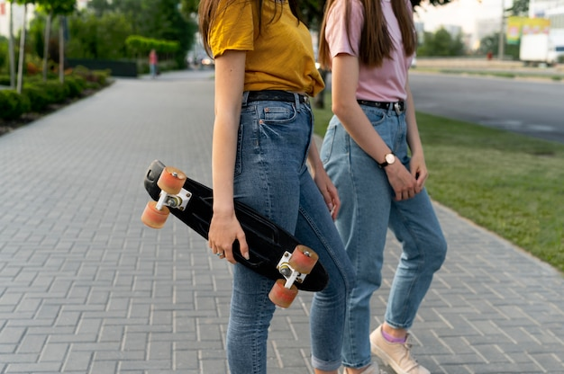 Female friends outdoors in the city with skateboard