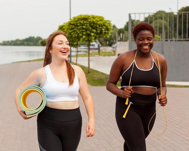 Подруги на открытом воздухе пытаются заниматься спортом