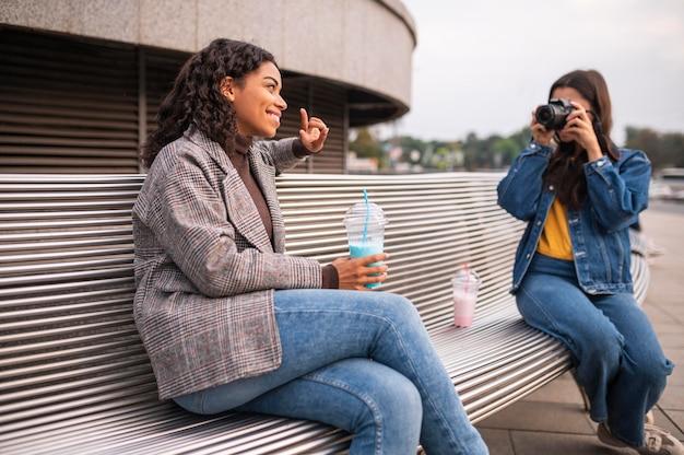 Amici femminili all'aperto con fotocamera e frappè