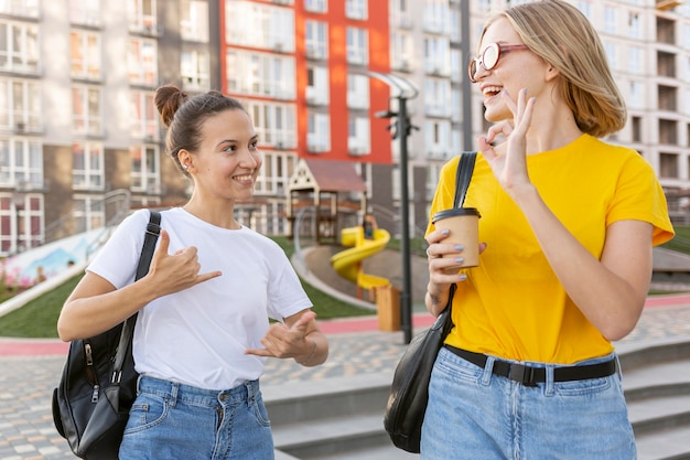 Female friends outside using sign language