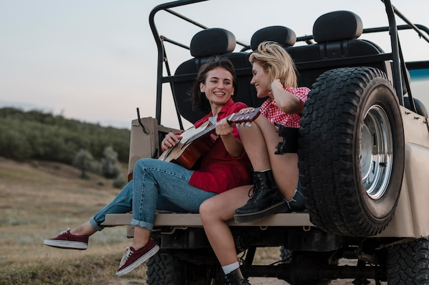 Amici di sesso femminile a suonare la chitarra mentre si viaggia in auto