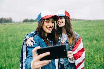 Женские друзья позируют на телефоне