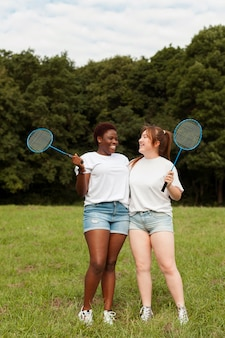 Female friends posing together outdoors with badminton rackets