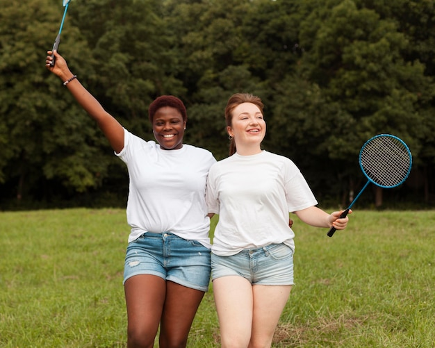 Female friends posing together outdoors with rackets