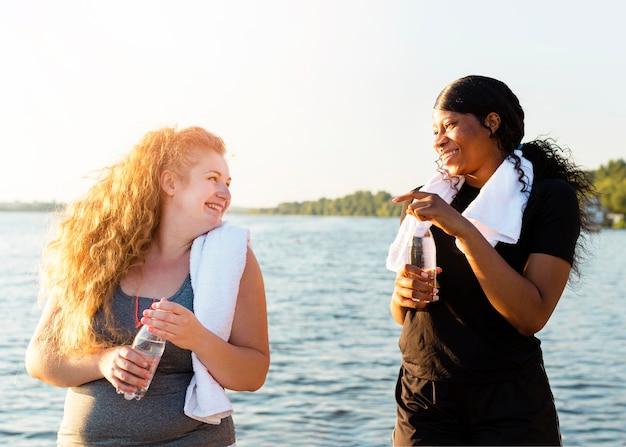 Amici femminili che riposa dopo l'esercizio in riva al lago