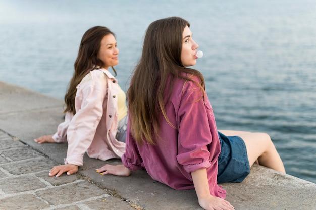 Amici femminili che riposa in riva al lago