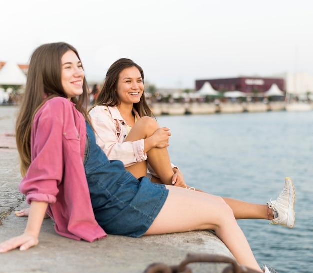 Amici femminili che riposano insieme in riva al lago