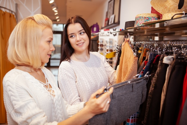 Female friends shopping together at clothing store