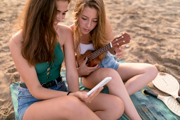 Female friends sitting at beach looking at mobile phone