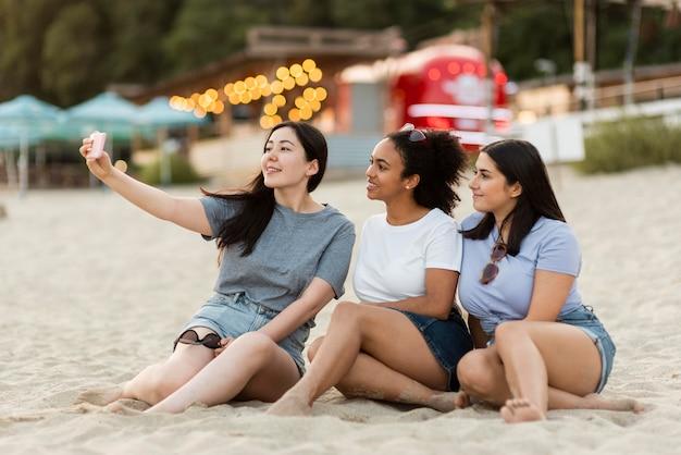 Amici femminili che si siedono sulla spiaggia e prendendo selfie