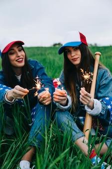 Amici femminili che si siedono nel campo con le decorazioni americane