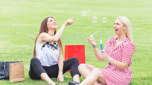 Female friends sitting on lawn playing with bubbles