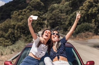 Female friends sitting on car hood taking self portrait