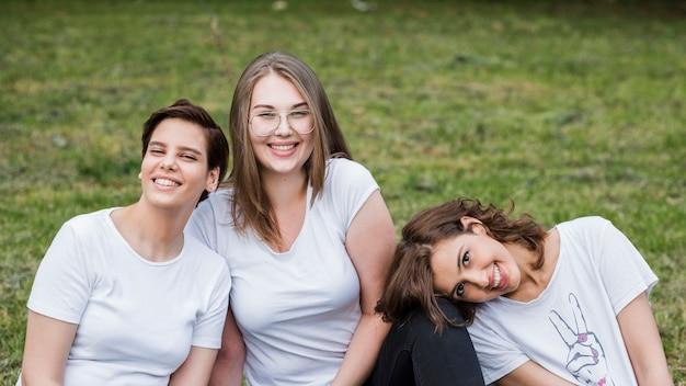Женщины друзей, сидя на траве, улыбаясь Бесплатные Фотографии