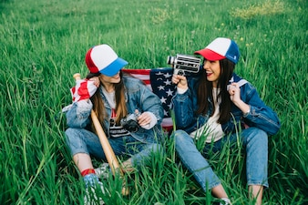 Female friends sitting on green grass in casual clothes