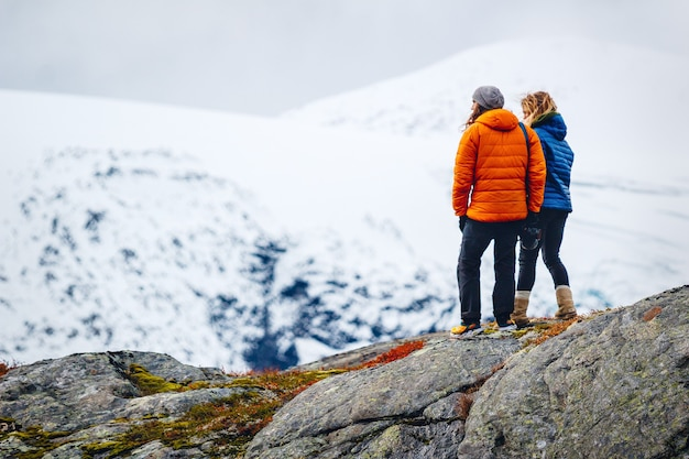 Female friends standing on top of a rocky mountain covered with snow