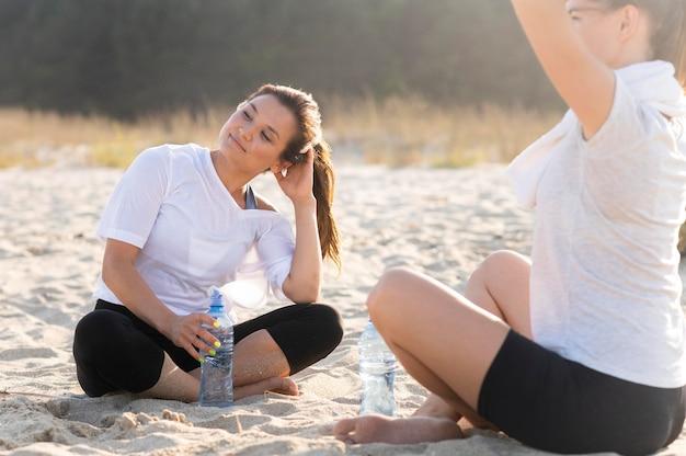 ビーチでの運動を休んでいる女性の友人