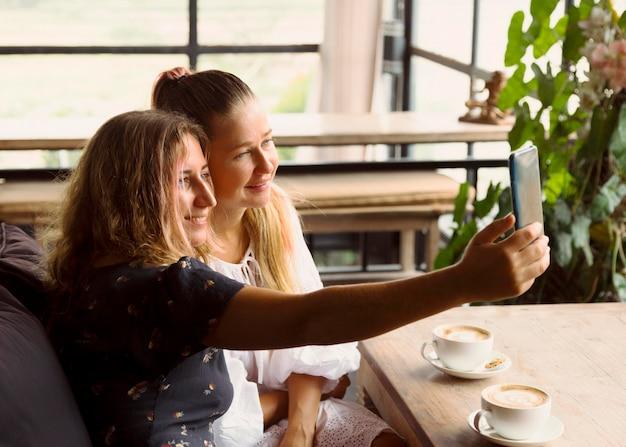 Подруги, делающие селфи за чашкой кофе