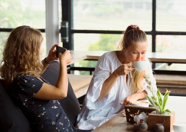 Amici femminili che scattano foto e bevono caffè
